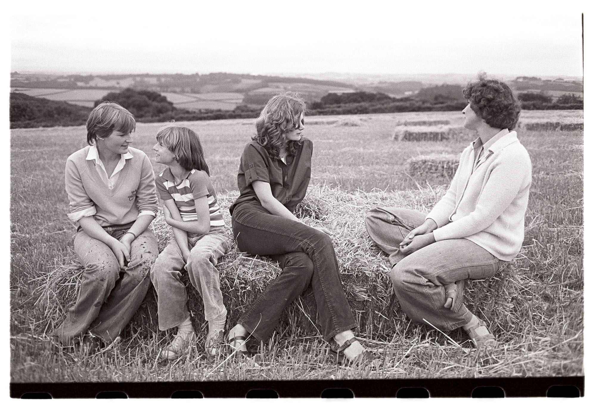 Women sitting on straw bales resting in field. <br /> [Kay Allin, two other women and a young girl sat on straw bales in a field at Ashwell, Dolton with a view of fields and trees in the background.]