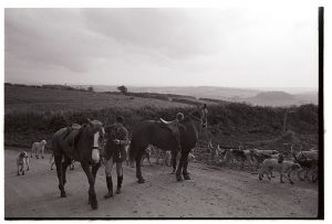 Dismounted riders in the road by James Ravilious