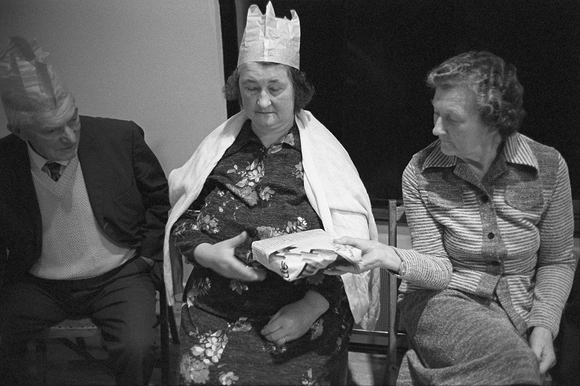 Pass the Parcel, games at Christmas party in village hall. <br /> [Two women and a man playing a game of pass the parcel at a Christmas Party in Beaford Village Hall. One of the women is wearing a paper hat.]