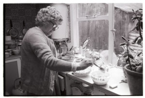 Mrs Hutchins making trifle by James Ravilious