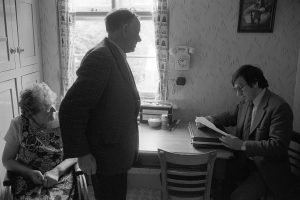 Dr Paul Bangay talking to an elderly couple at home by James Ravilious