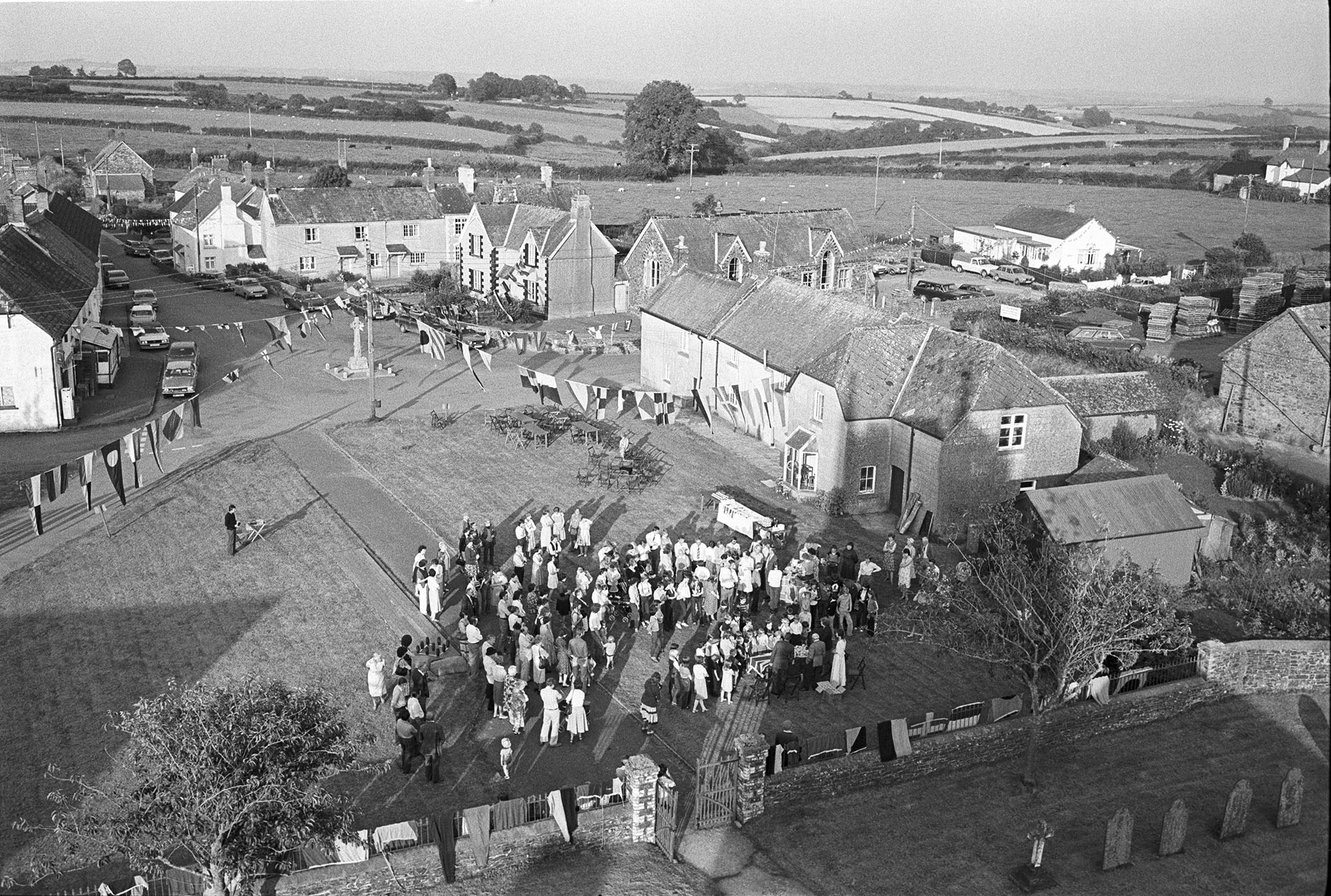 Royal Wedding. Assembling for presentation of commemorative mugs. View from church tower.<br /> [A view taken from Ashreigney Church tower of people gathered on the green for the presentation of mugs for the Royal Wedding of Prince Charles and Lady Diana Spencer. A view of the village decorated with flags and bunting is visible behind the crowd.]