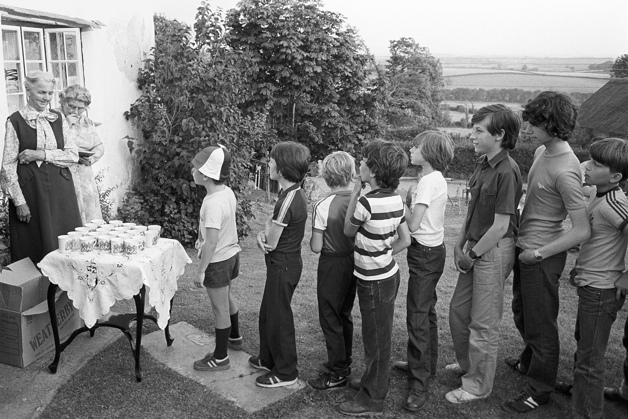 Royal Wedding. People queuing for royal mugs in front of cottage.<br /> [Children queueing up in a garden at Iddesleigh for the presentation of mugs to commemorate the Royal Wedding of Prince Charles and Lady Diana Spencer. Two ladies are waiting to present the mugs.]