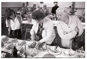 Woman judging cakes at Dolton Flower Show by James Ravilious