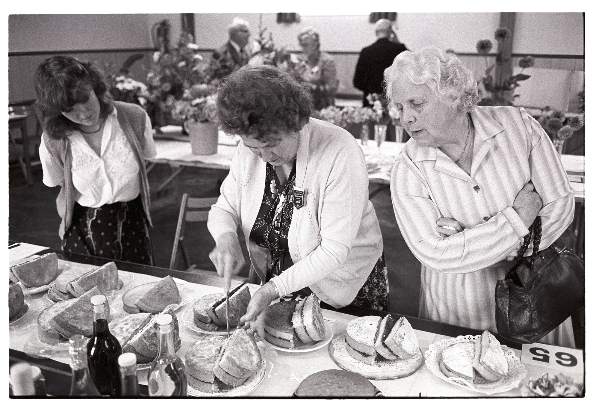 Woman judge. Judging cakes at village Flower Show.<br /> [Mary Turner judging cakes at the Dolton Flower Show in Dolton Village Hall, with her daughter Pip Turner and another woman watching her.]