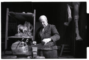 Horace Baker sharpening his chainsaw by James Ravilious