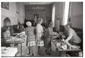 Women looking at cake and produce stalls by James Ravilious