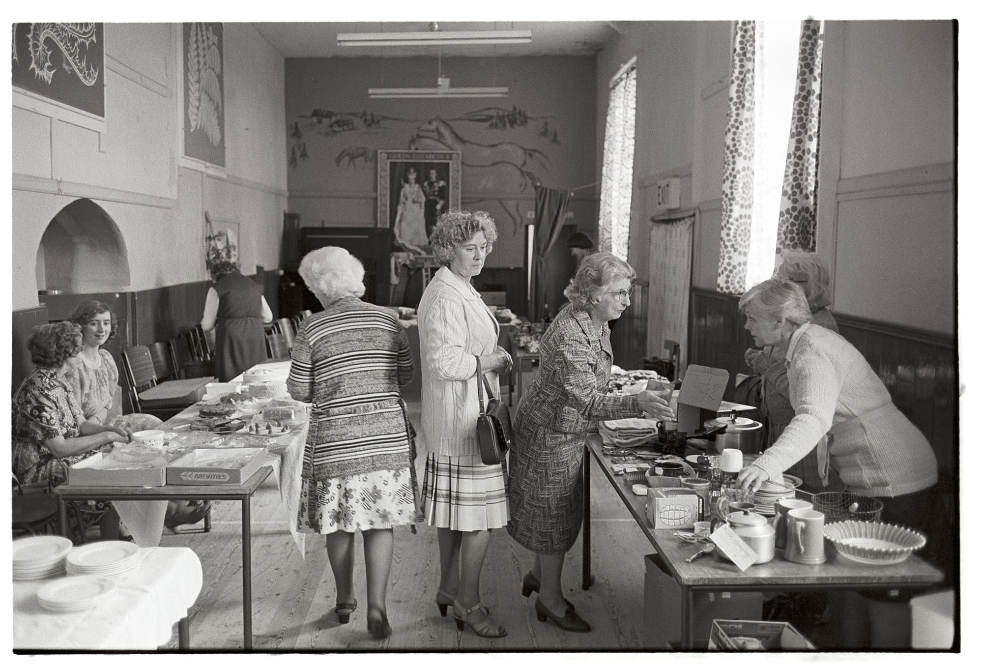 Stalls in village hall, women looking at cakes and produce. Dresses and cardigans. <br /> [Women looking at cake and bric-a-brac stalls at Roborough Fair in Roborough Village Hall. The walls are decorated with pictures, including a royal portrait at the far end of the hall.]