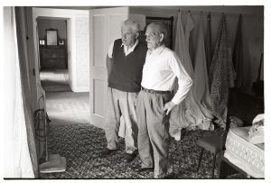 Lloyd Mitchell and Jim Hutchins standing in a bedroom on viewing day by James Ravilious