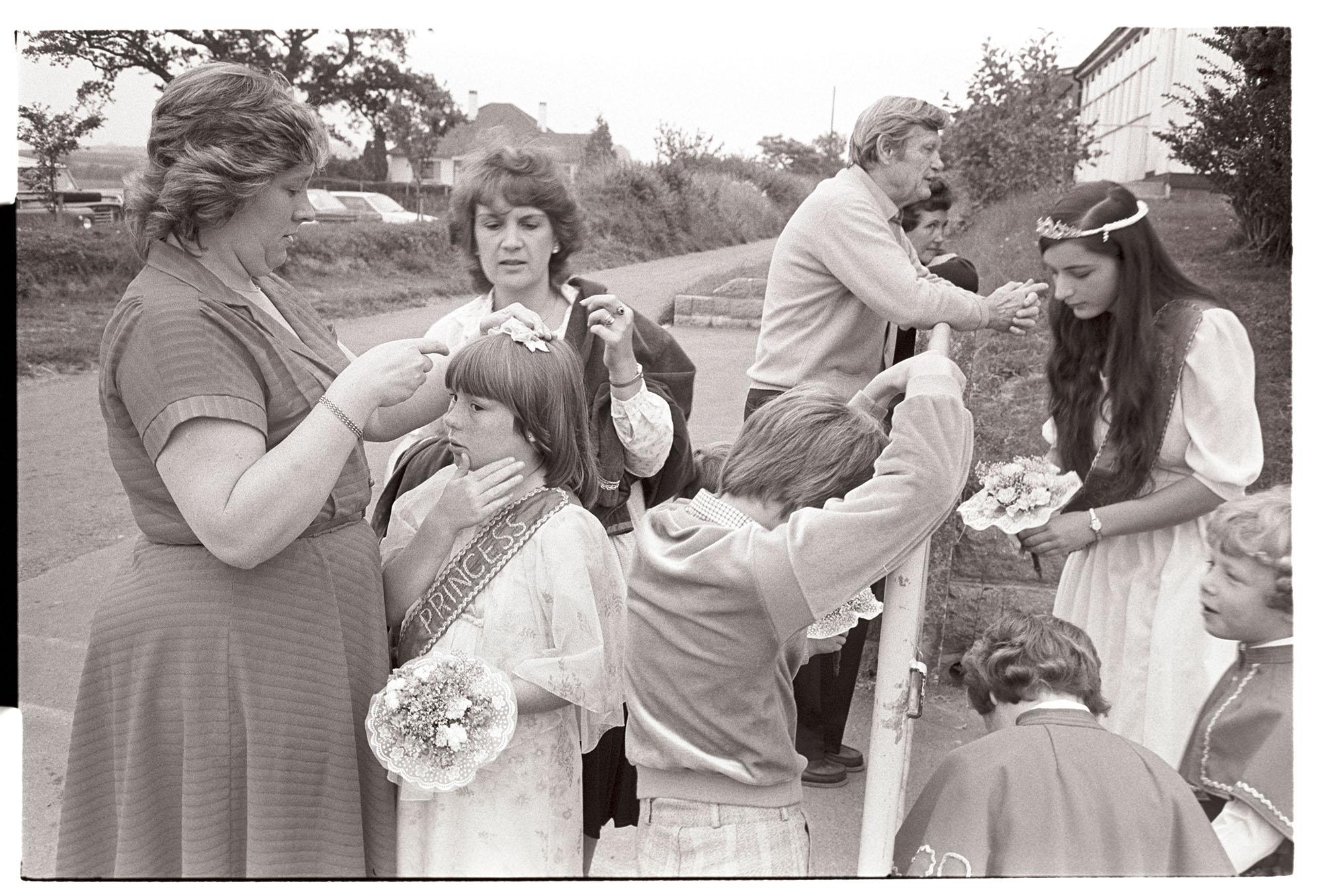 Fair Queen and attendants preparing for parade through village. <br /> [Chulmleigh Fair Queen, Fair Princess and attendants getting ready for the parade through the town at Chulmleigh Fair. A woman is preparing one of the princess's hair.]