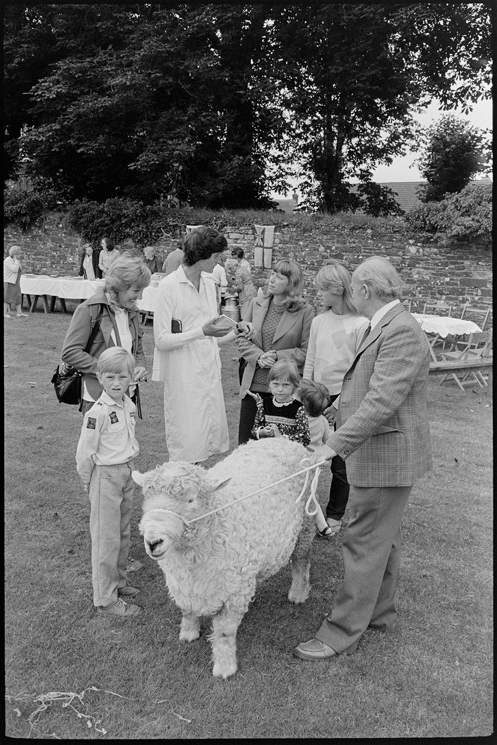 Village revel, fete, women at cake stall, guessing weight of ram, side shows, brass band.<br /> [Women and children at Beaford Revel guessing weight of a ram, on Beaford Village Green. A man is holding the ram. Stalls and trees can be seen in the background.]