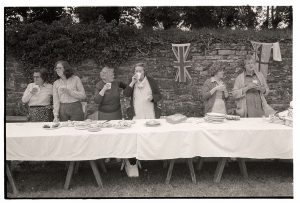 Women at the cake stall after the village fete by James Ravilious
