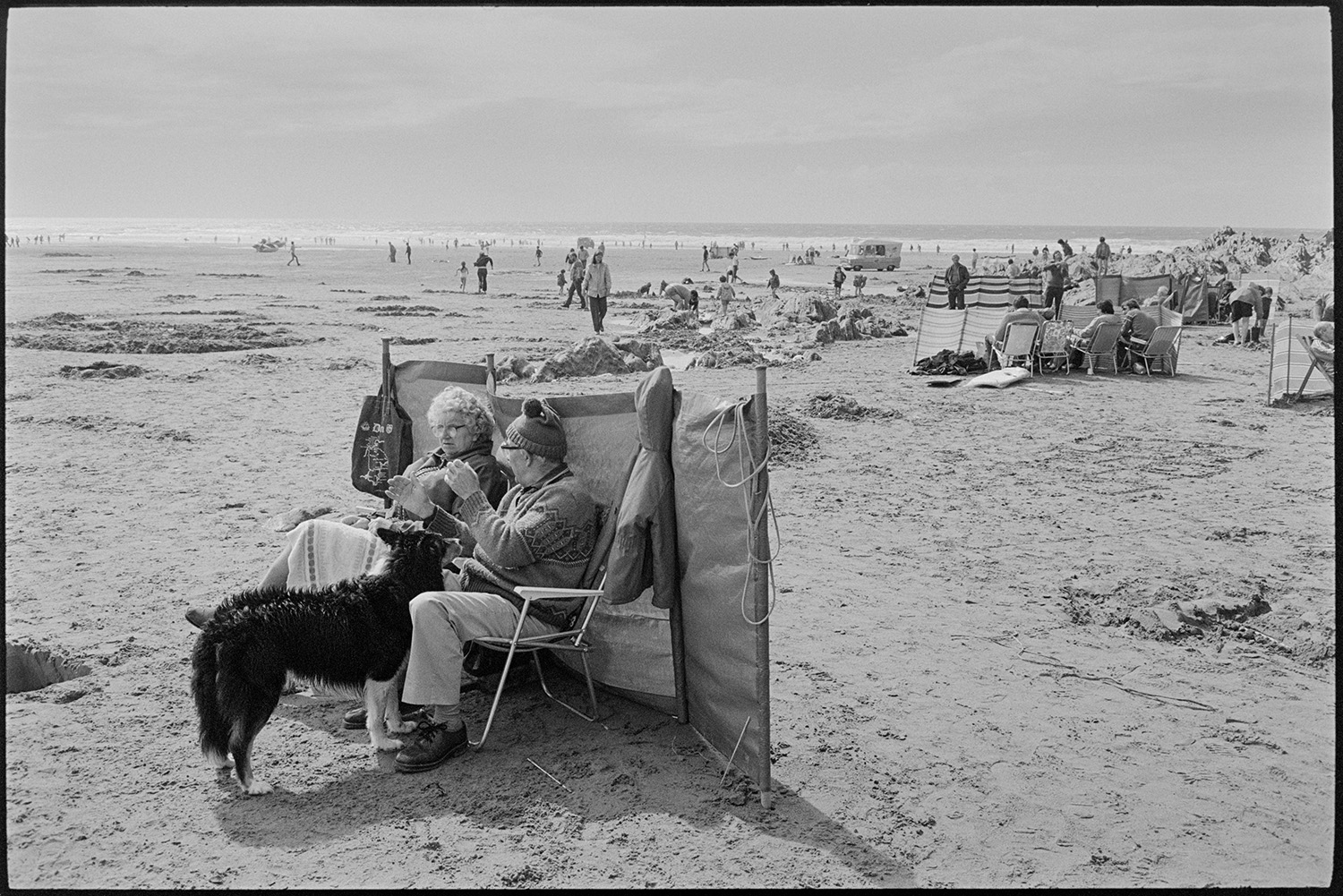 Beach scenes, people sitting behind windbreaks.<br /> [A couple sitting behind a windbreak with their dog on Woolacombe beach. The man is wearing a woolly hat. Other holidaymakers, an ice cream van and the sea are visible in the background.]