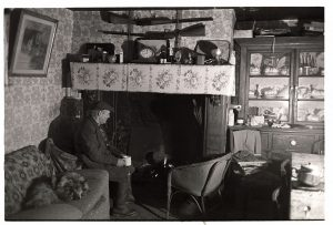 Ivor Brock seated in front of the fireplace at Parkers Down by James Ravilious