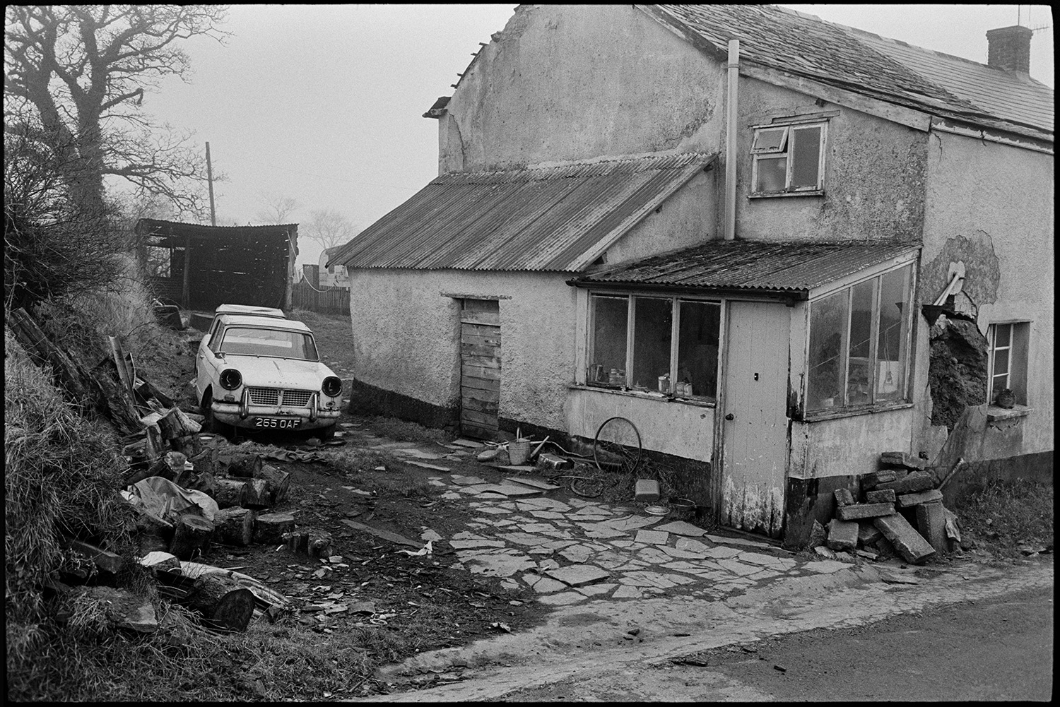 Yard of run down cottage with derelict car. <br /> [A derelict car parked next to a run down cottage near Winkleigh. Logs, a bicycle wheel, watering can and pile of stonework can be seen in the yard by the cottage. The cottage porch has a corrugated iron roof.]