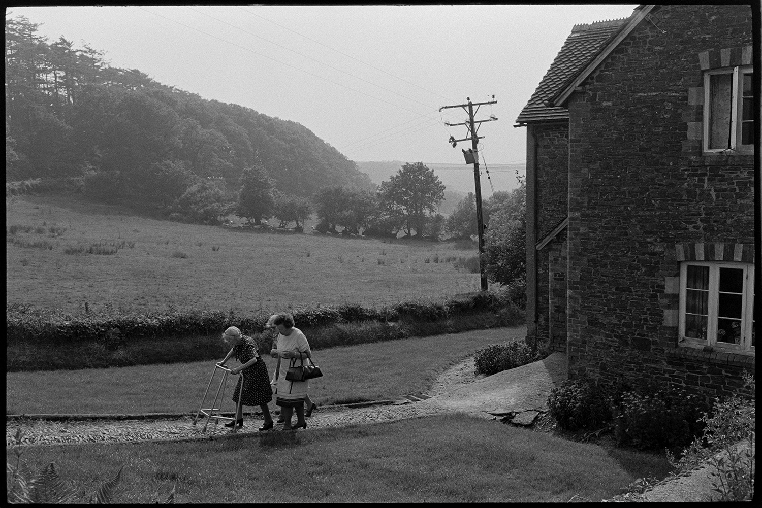 Elderly women with walking frame leaving cottage. <br /> [Two women helping another woman using a walking frame walk along a cobbled path away from a stone cottage at Wordens Cottages, Kingscott. A field with trees can be seen in the background.]