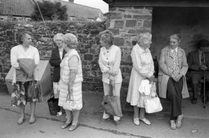 Women waiting for the bus on Friday market day by James Ravilious