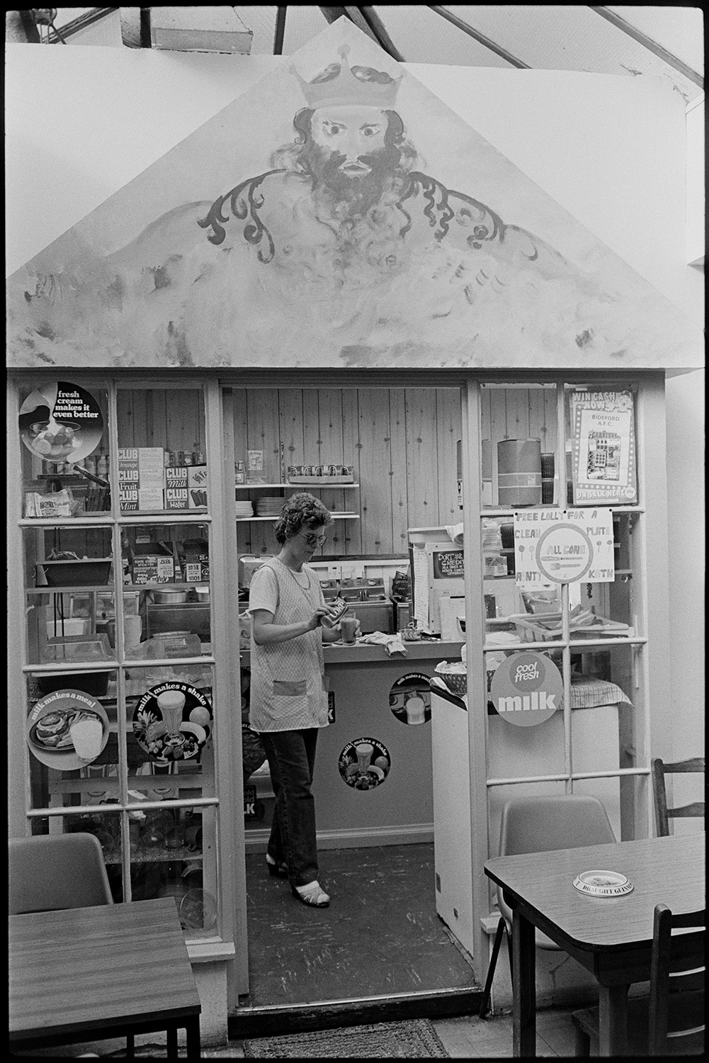 Front of cafe with mural painting. <br /> [The shop front of a café with a mural painting in a covered market at Bideford. A woman is pouring a glass of coca cola inside the café. Posters can be seen on the café windows.]