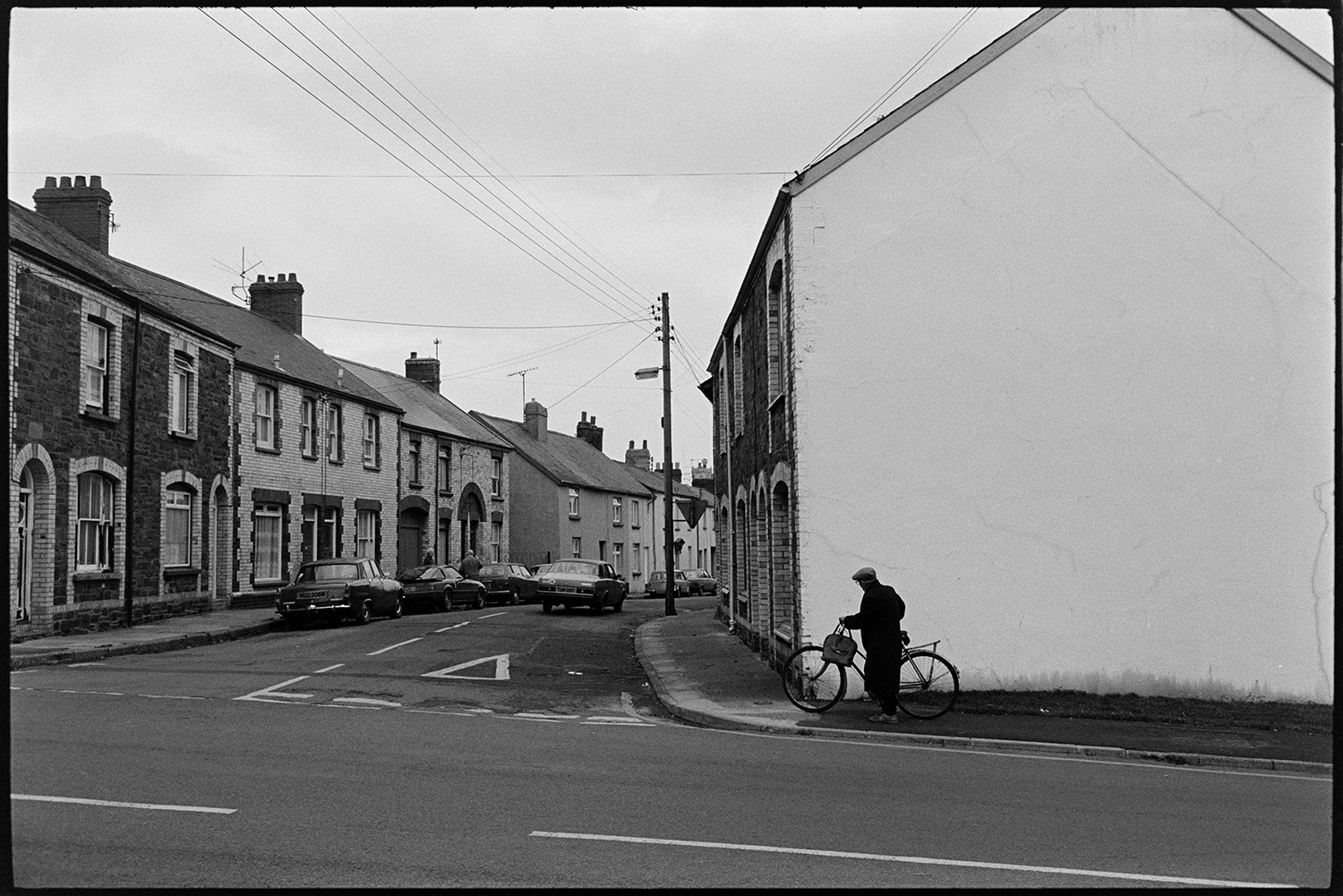 Street, man with bicycle.<br /> [A man holding a bag and pushing a bicycle on the pavement of a street with terraced houses in Torrington. He is approaching a road junction.]