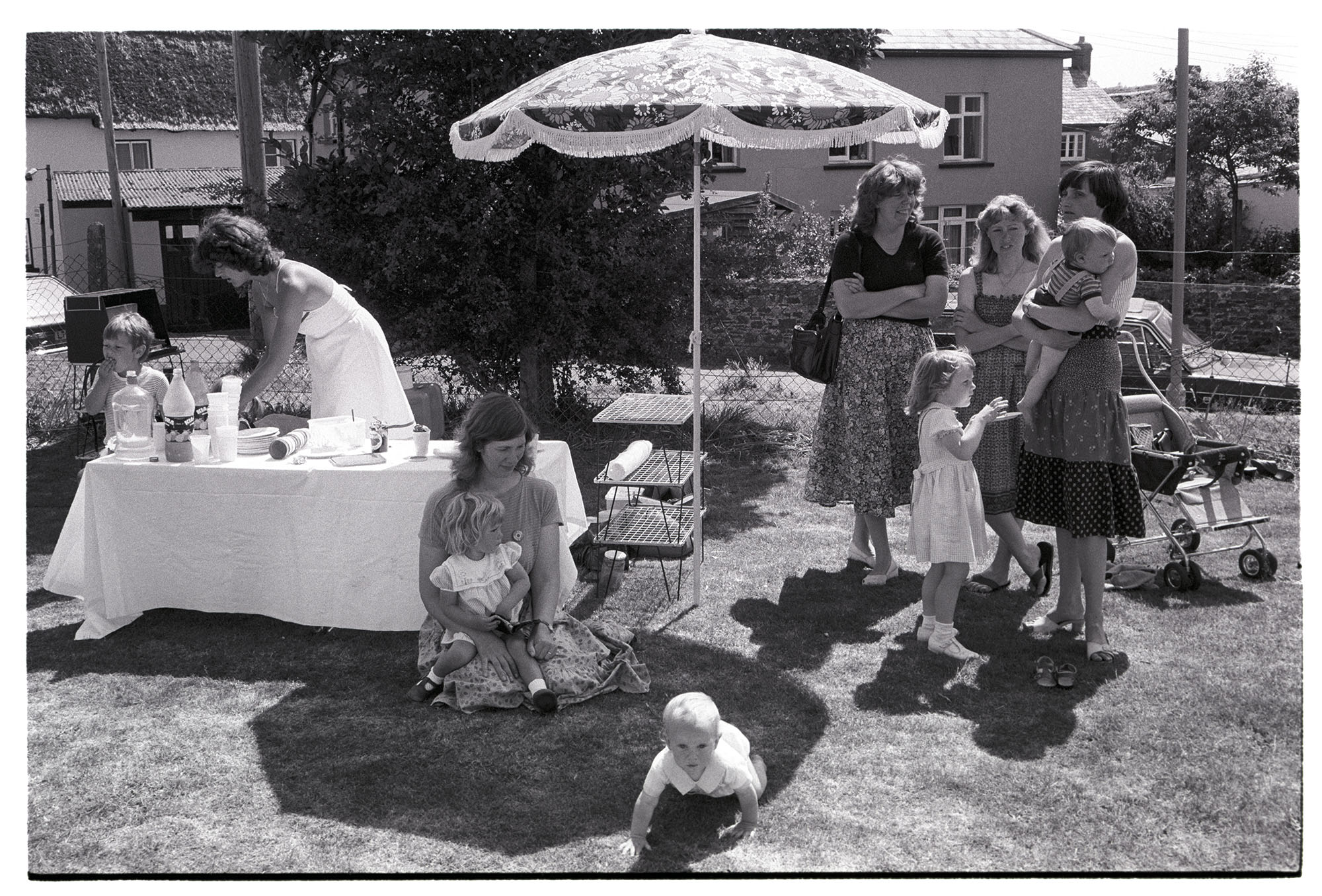 Sports day, women mothers with babies, children chatting and serving refreshments. <br /> [Women and children stood chatting by a refreshment stall and parasol at Dolton Sport Day. Catherine Simmons is sat on the ground with a child and a baby.]