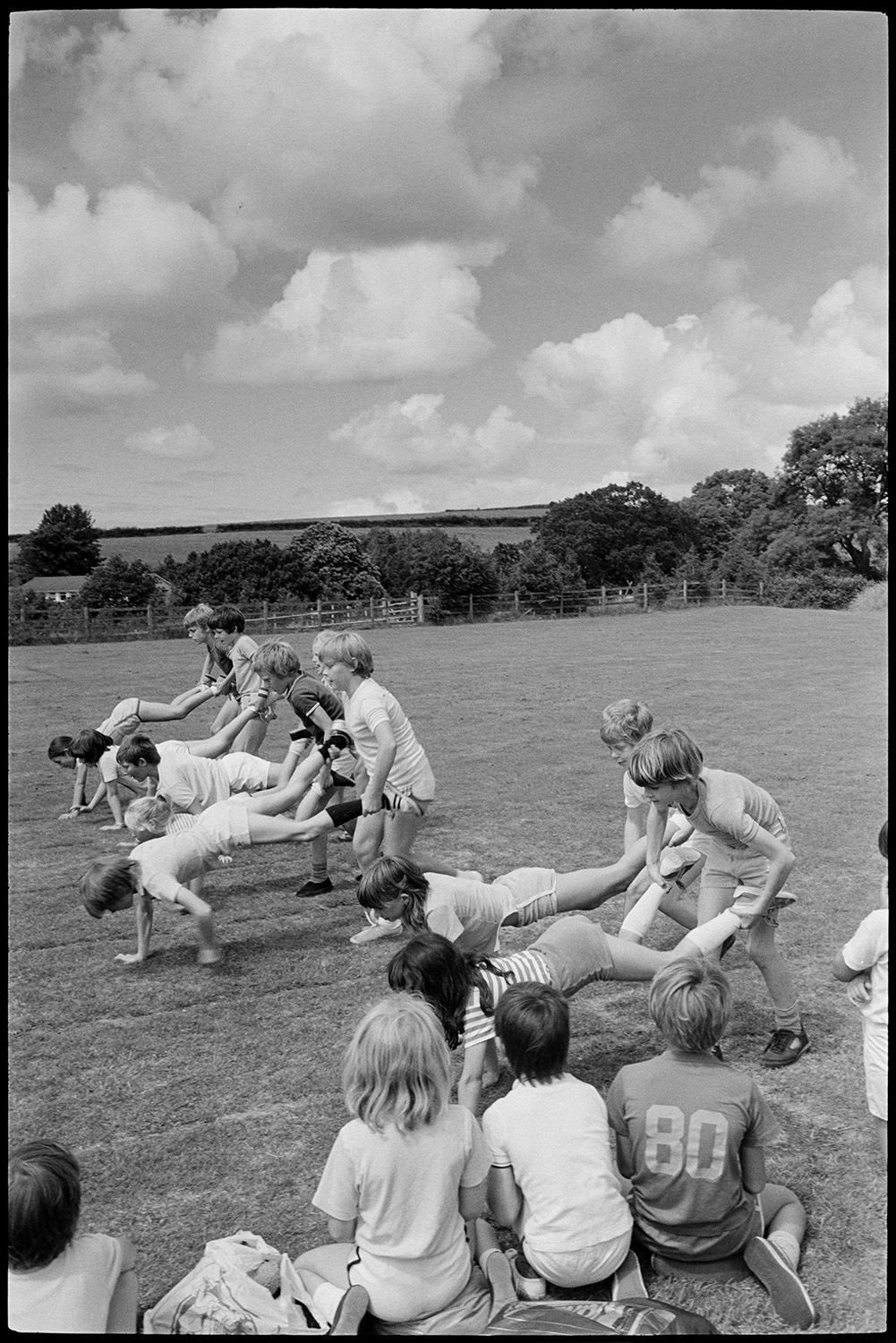 School sports day, children running races.<br /> [Children participating in a wheelbarrow race at the Dolton Primary School Sports Day. In the background are trees surrounding the field and clouds are in the sky.]