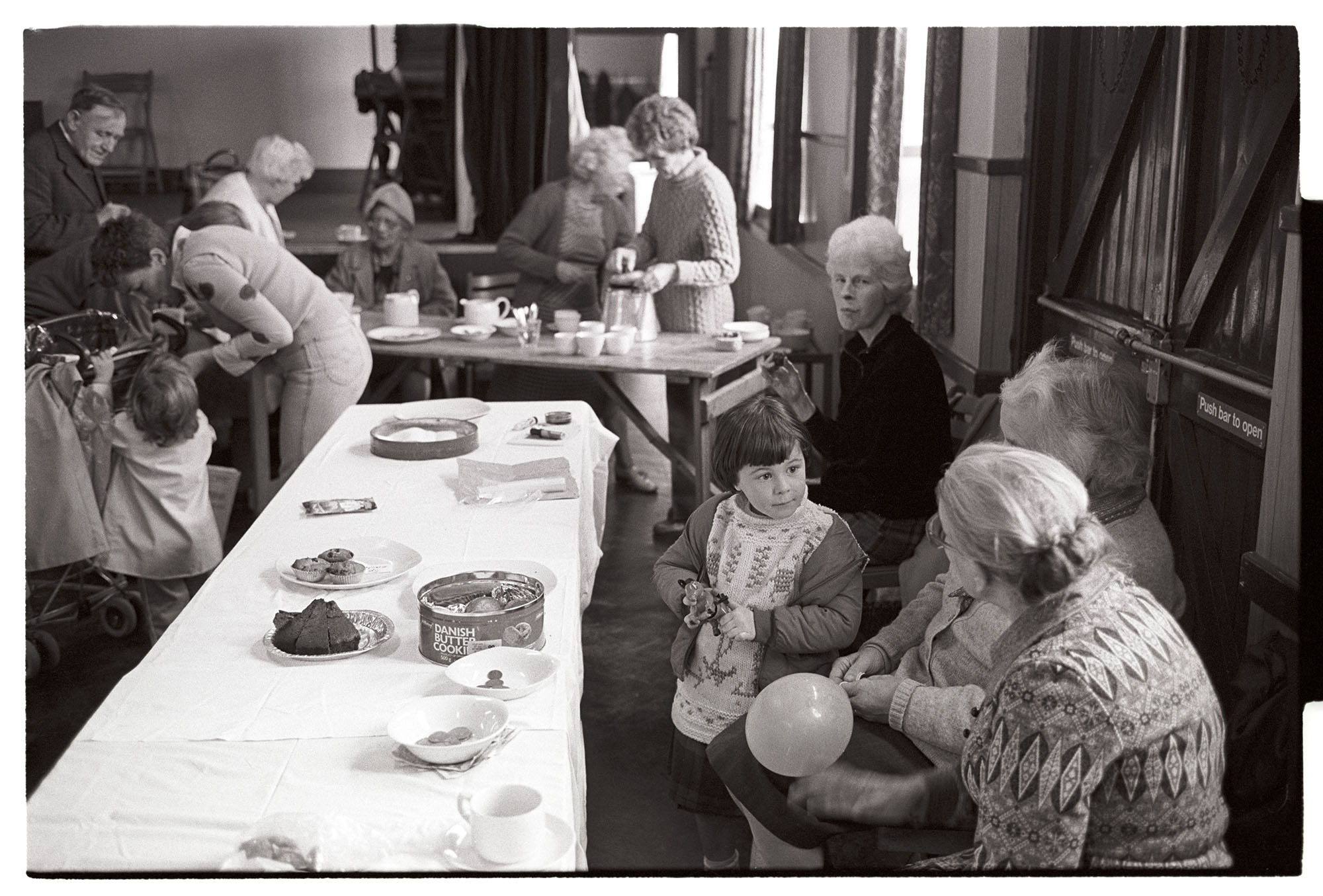 Elderly women and child at playgroup coffee morning. <br /> [Women and children at a coffee morning at Dolton playgroup in Dolton Village Hall. Two women are serving teas and coffee in the background and a young child, Jenny Agate, is talking to two older women in the foreground. One of the women is holding a balloon and cakes are on the table.]