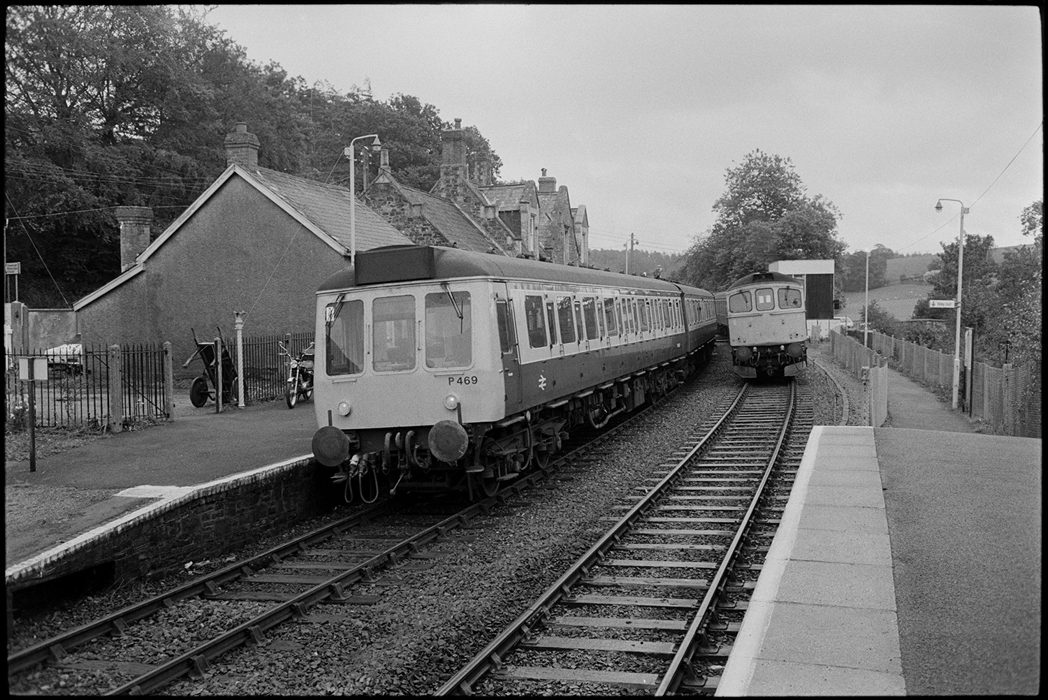 Train waiting at station other diesel train passing.<br /> [A diesel train waiting at Kings Nympton station for another diesel train to pass. Station buildings, platforms and trees can be seen in the background. A motorbike is parked on the platform.]
