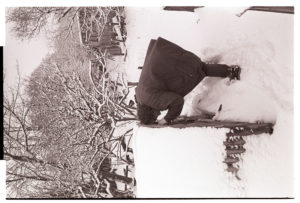 Olive Bennett checking stock in snow by James Ravilious