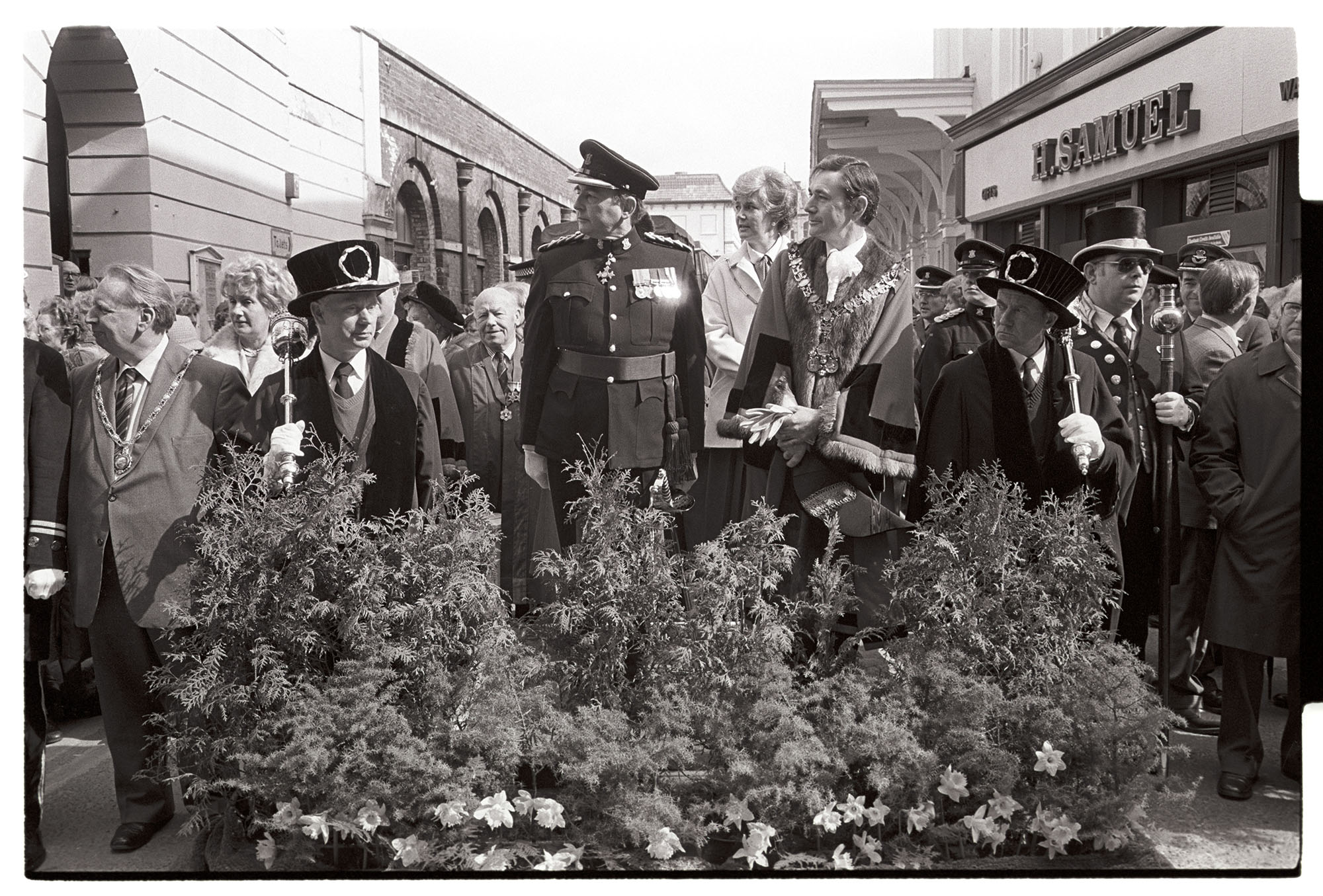 Mayor and officers, dignitaries at march past of regiment being given freedom of city? <br /> [The Mayor, service personnel and other officials and dignitaries stood in Barnstaple High Street, behind a flower bed, watching a regiment march past who are being given the freedom of the town. The shop front of H Samuel, Jewellers, is visible in the background.]