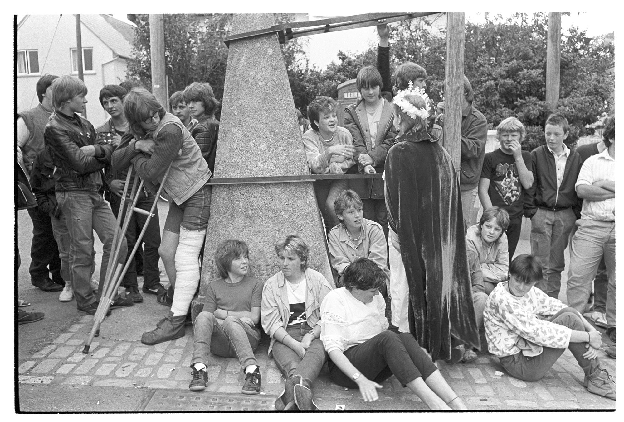 Crowd of young people around village pump at start of Fair. <br /> [A group of young men and women stood and sat around the village pump at the start of Winkleigh Fair. The Fair Queen is talking to some of the people and one young man has a pair of crutches.]