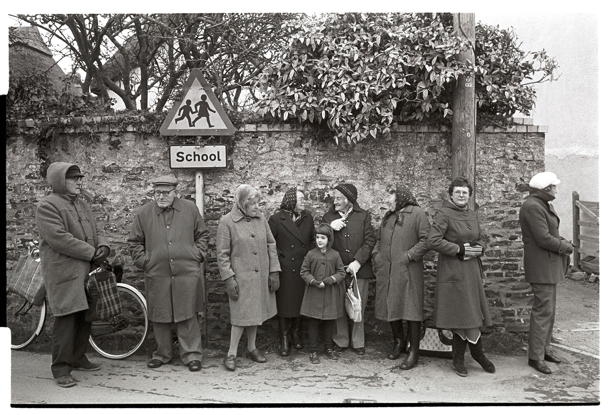 Pancake race in village street spectators standing against wall at finish.<br /> [A group of people and a child, Ella Ravilious, standing against a wall in Fore Street, Dolton, on Shrove Tuesday, waiting for the finish of the village pancake race. They are wearing coats against the cold and one man is stood by a bicycle.]