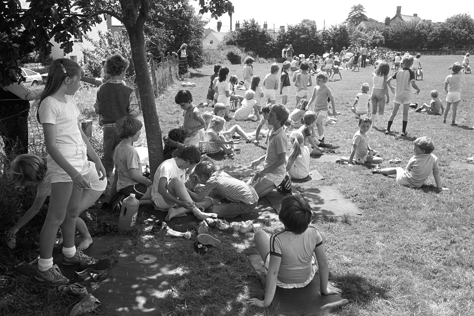School sports day, races, people sitting in sun and shade waiting to run. <br /> [Children sitting in the sun and under the shade of a tree at Dolton School Sports Day. In the background children are taking part in a wheelbarrow race.]