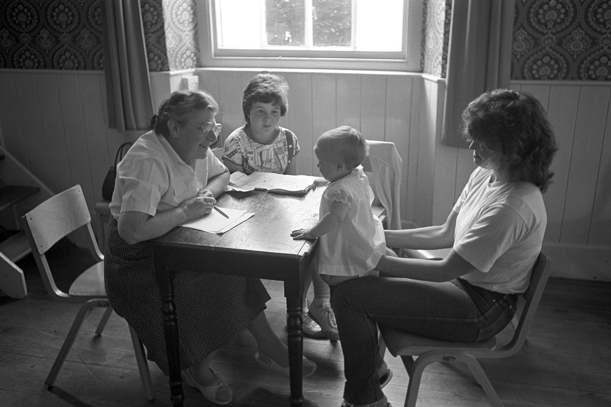 Fair, Baby competition, woman judging baby held by mother. <br /> [Sister Irene Morris judging a baby sat on its mother's lap in the baby competition at Chulmleigh Fair in Chulmleigh Town Hall.]