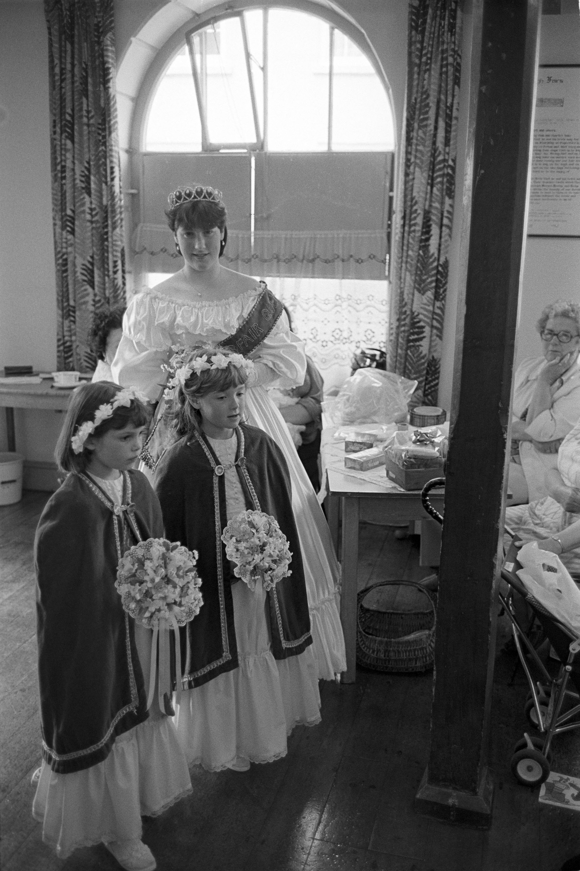 Fair Queen and attendants in town hall. <br /> [Emma Bending, Chulmleigh Fair Queen, with two attendants in Chulmleigh Town Hall before Chulmleigh Fair. They are all holding bouquets of flowers.]