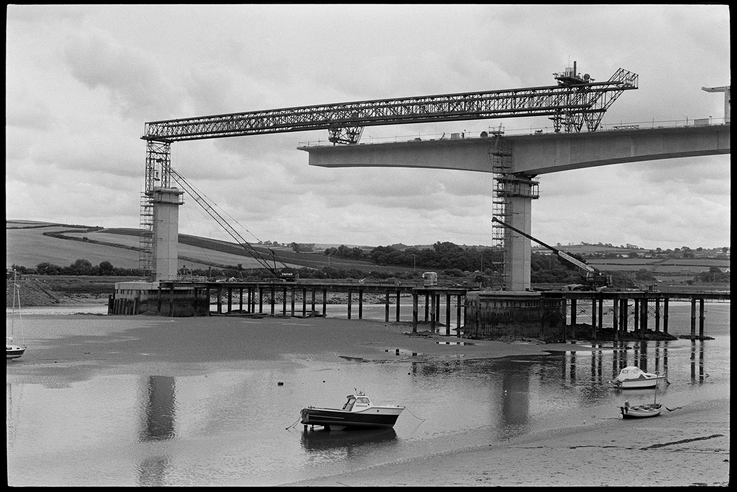 New bridge under construction. Boat and mudflats.<br /> [Bideford New Bridge under construction over the River Torridge. Scaffolding and working cranes are visible and small boats can be seen on the mudflats. A landscape of fields is visible in the background.]