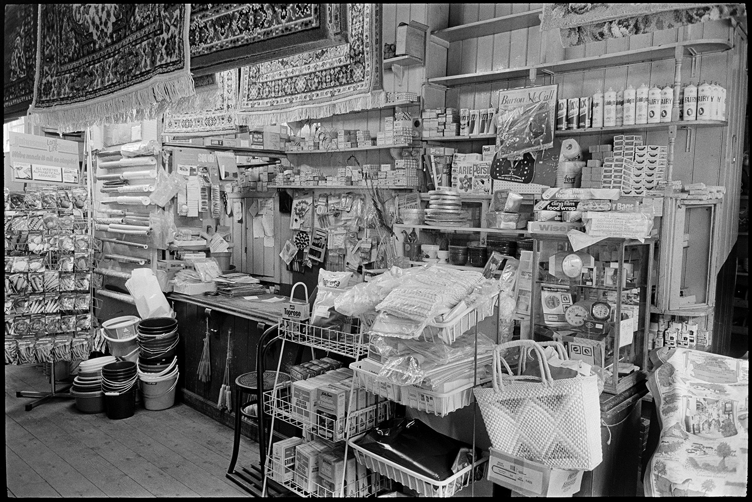 The interior of Ellacott's Ironmongery shop in Market Street, Hatherleigh. The shop counter is visible and various goods are on display, including seeds, buckets, rugs and clocks.