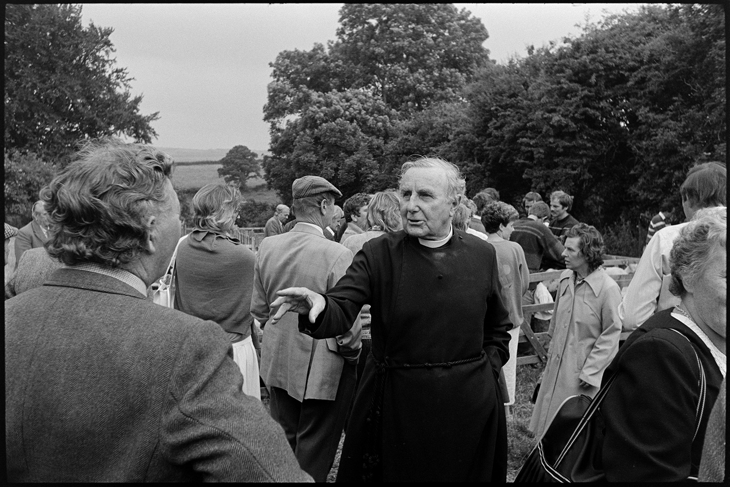 Sheep sale at fair, onlookers and vicar chatting to crowd.<br /> [The Reverend John Richards talking to a man at the sheep sale at Chulmleigh Fair. Other people are gathered around in the background.]