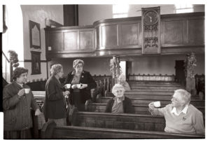 Minister Elaine Marsh with flower arrangers by James Ravilious