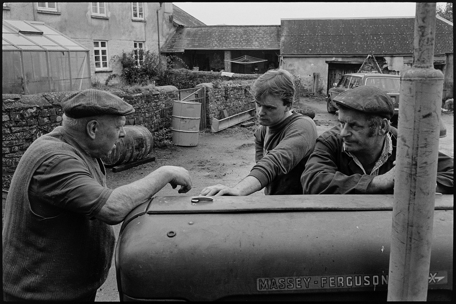 Farmers pressing cider in barn. Baskets of apples poured into crusher.<br /> [Bill Bending, on the left, and two other men, talking in the farmyard at Spittle, Chulmleigh. They are standing by a Massey Ferguson tractor, with farm buildings in the background.]