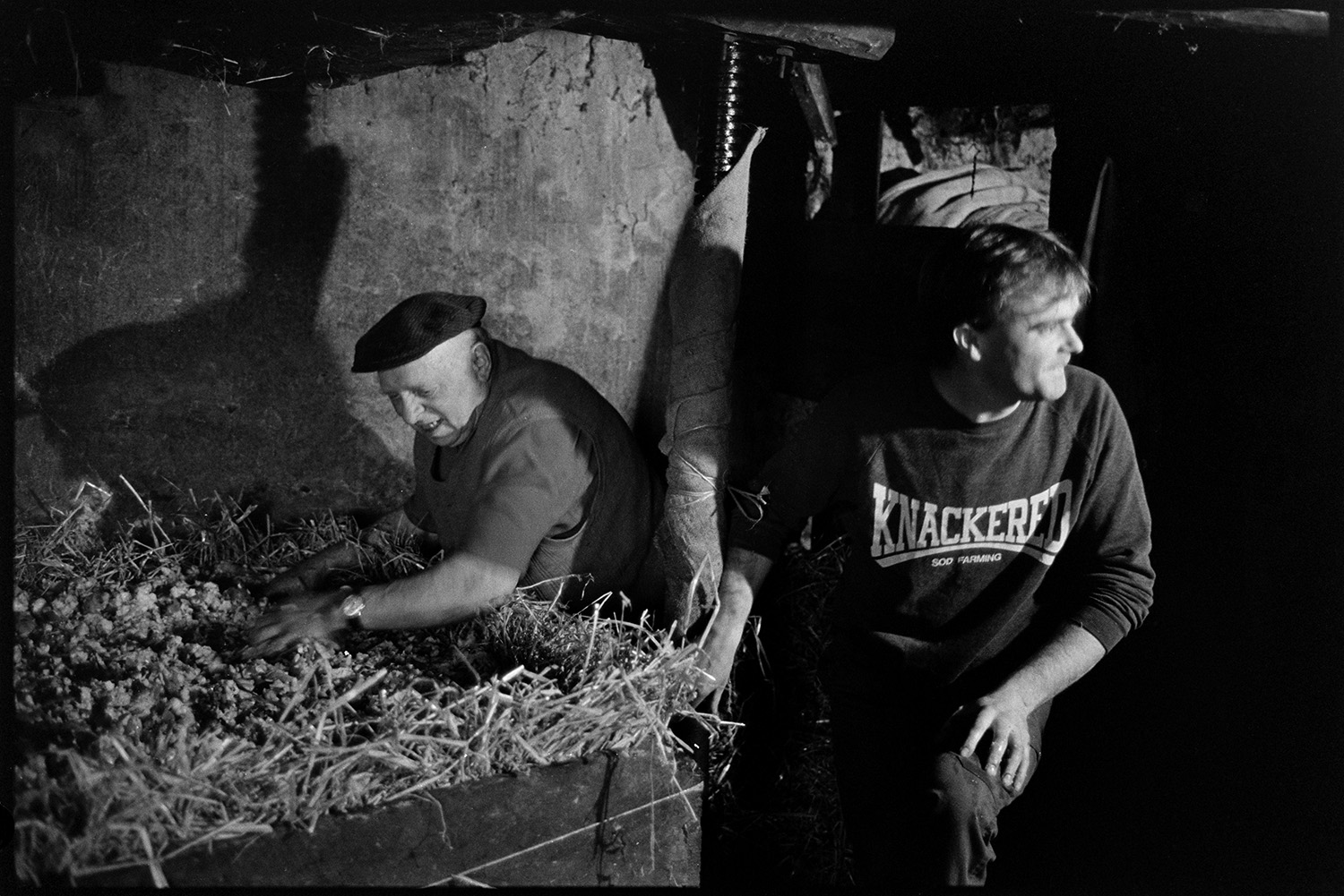 Farmers pressing cider in barn. Baskets of apples poured into crusher.<br /> [Bill Bending, wearing a cap, showing a younger man, Mr Down, how to use a cider press at Spittle, Chulmleigh.]