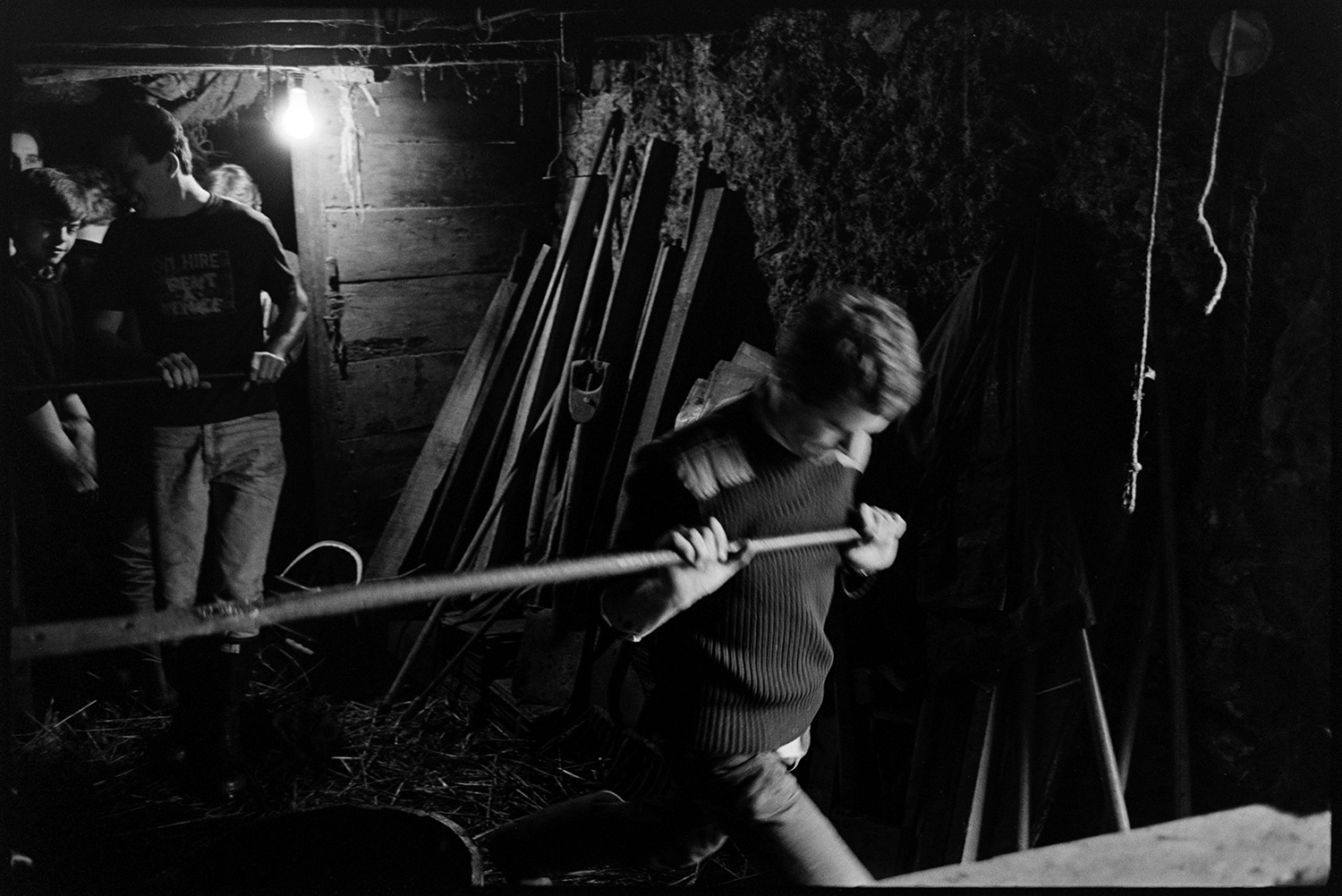 Men pressing cider and trying it out.<br /> [Men from the Down family pressing cider in a barn at Spittle, Chulmleigh. One man is pushing a metal bar to turn the cider press, while others watch in the background.]