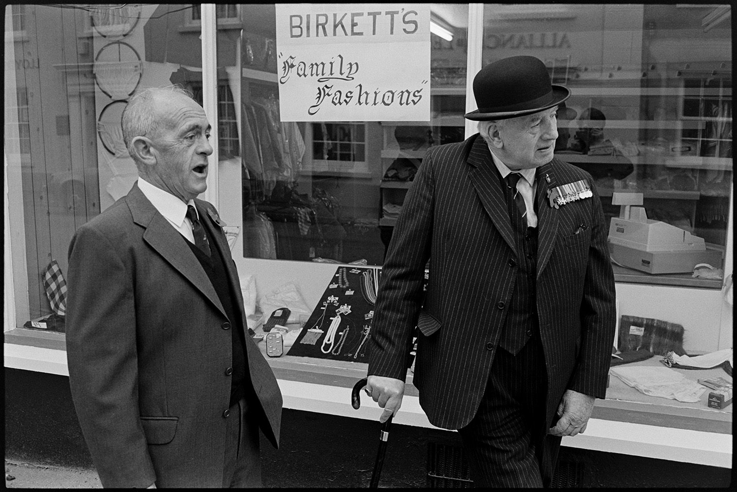 Men and women assembling for Remembrance Sunday Parade, some with bowler hats and medals.<br /> [Two men attending the Remembrance Sunday Parade at Chulmleigh. One man is dressed in a suit with a bowler hat and is wearing medals. They are standing outside the shop front of Birkett's clothes shop in Fore Street.]
