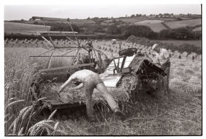 Farmers unblocking jammed reap and binder by James Ravilious