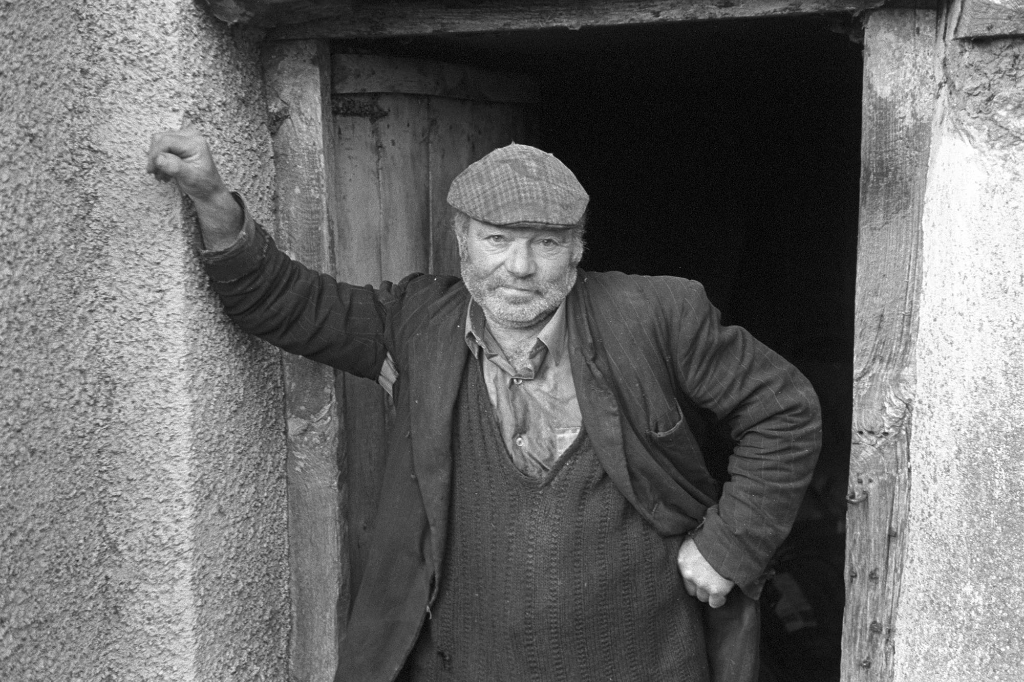 Orchards, Devon, man facing camera in doorway in cap. <br /> [Reg Holland stood in a wooden doorway wearing a cap, at Newhouse, Ashreigney.]