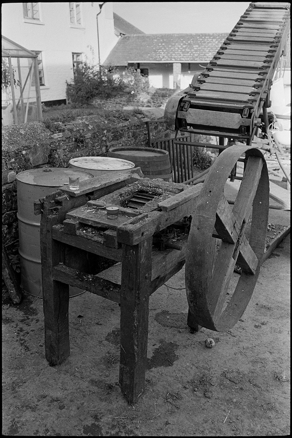 Pressing cider on farm, crusher and barrel. <br /> [Farm machinery, including barrels, an elevator and an apple crusher, in front of the farmhouse at Spittle Farm, Chulmleigh.]