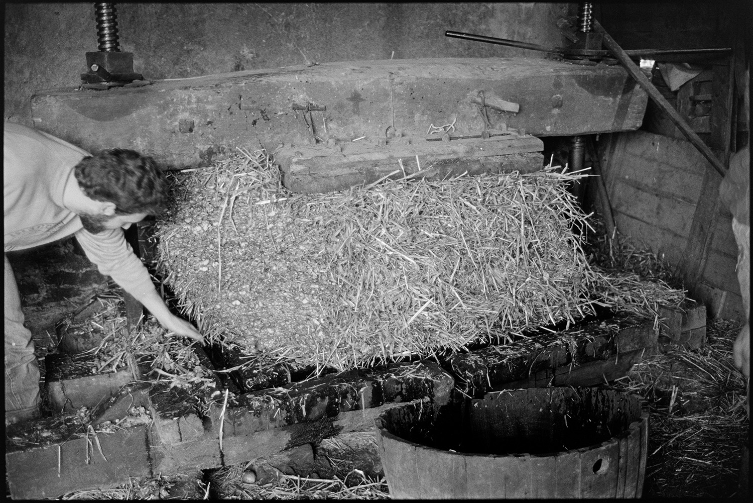 Pressing cider on farm, crusher and barrel. <br /> [A man, possibly from the Down family, operating a cider press in a barn at Spittle Farm, Chulmleigh. The press is squashing the cheese, layers of apple pulp and straw, and cider is running into a barrel underneath.]