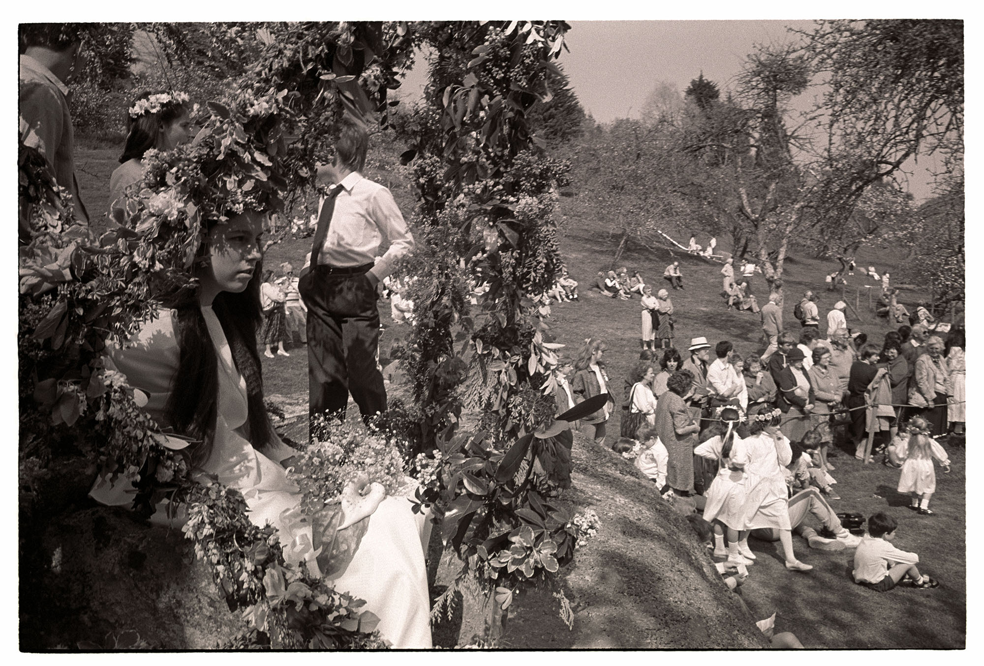 Orchards, May Queen enthroned in flower bower on rock. <br /> [May fair celebration in an orchard in Lustleigh. The May Queen is sat in a flower bower on a large rock. Spectators are stood and sat in the orchard. Some girls, possibly May Queen attendants, are wearing floral headbands.]