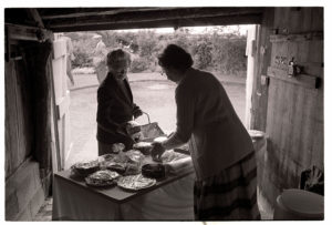 Women at a garden party cake stall by James Ravilious