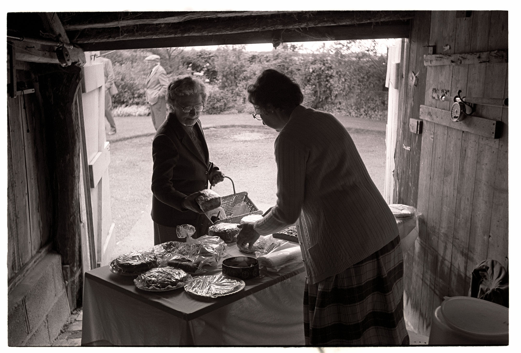 Open garden, with cake stall in garage. <br /> [Two women at a cake stall in a garage at a garden party at Highdown, Ashreigney. The garden party was hosted by Moggie Dew.]
