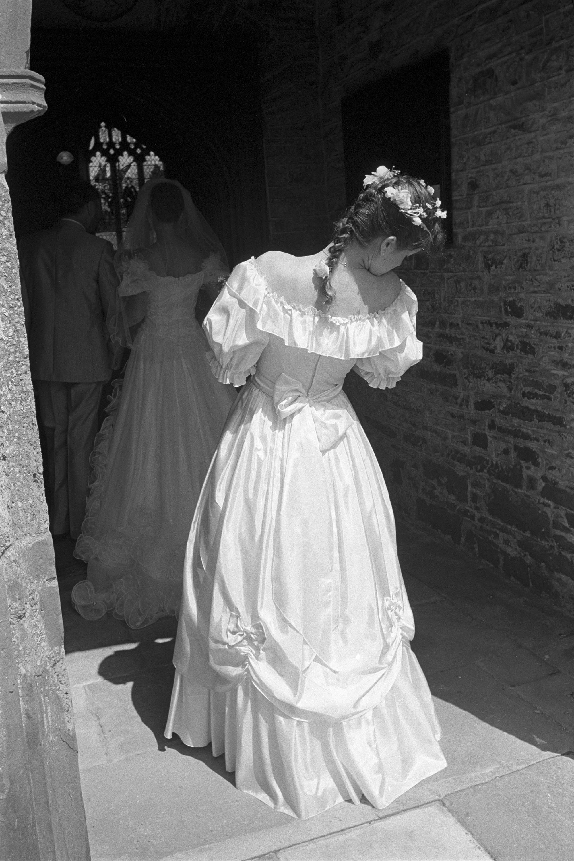 Wedding, bridesmaid about to enter church. <br /> [A bridesmaid entering Chulmleigh Church, for a wedding, behind the bride. A stained glass window can be seen inside the church, from the doorway.]